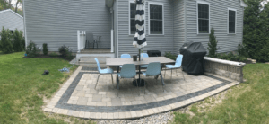 Rectangular patio made with concrete pavers with a table and six chairs on top of it